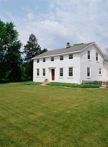EXTERIORS: Two-story single family stucco Georgian Colonial farmhouse, built in 1841, restored, lawn, plain and simple, vertical version with more picket fence to right, ground cover near house
